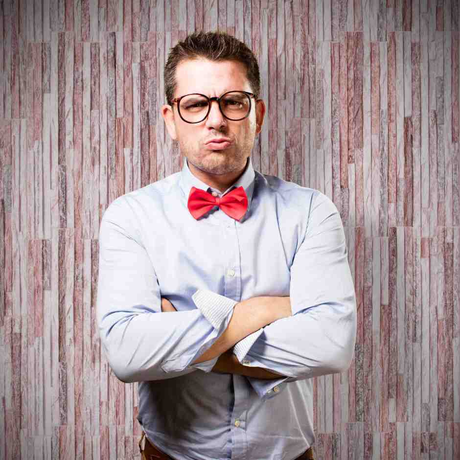 Man wearing a red bow tie. Looking upset.