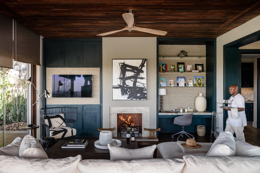 Hillside-Suite-Singita-Sasakwa-Lodge-Lounge-Area-with-Fireplace-and-Staff